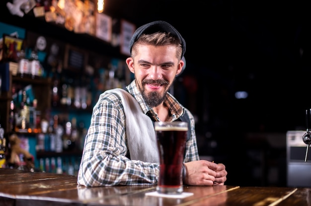 Charming barman pouring fresh alcoholic drink into the glasses in the nightclub