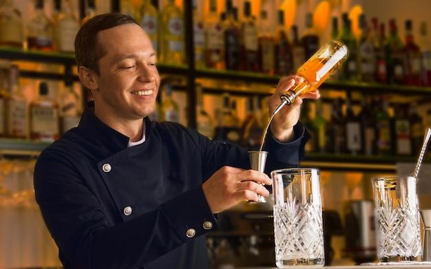 매력적인 바텐더는 병의 알코올을 지거에 부어 혼합 그릇에 혼합 음료를 만듭니다