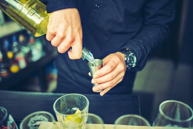 매력적인 바텐더가 병에 담긴 술을 지거에 붓는다