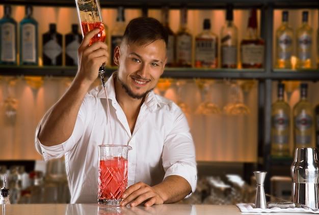 매력적인 바텐더는 병의 알코올을 믹스 컵에 부어 믹싱 그릇에 혼합 음료를 만듭니다