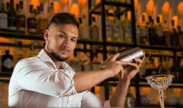 Очаровательный бармен держит шейкер и смотрит в камеру