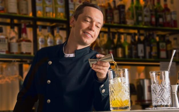 매력적인 바텐더는 훌륭한 음료를 요리하기 위해 지거에서 믹싱 글라스에 알코올을 붓고 있습니다