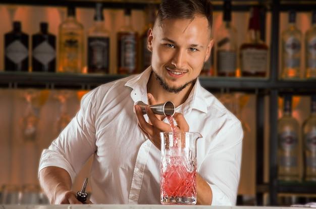 魅力的なバーテンダーがジガーから氷で満たされたミキシンググラスにアルコールを注ぎます