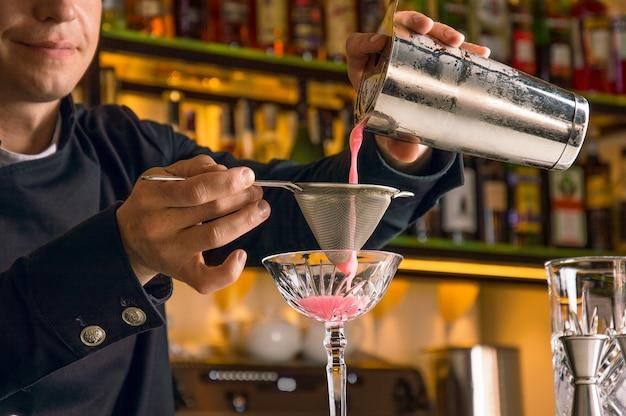 매력적인 바텐더가 맛있는 칵테일을 준비합니다. 스트레이너를 통해 음료를 걸러내고 칵테일 글라스에 따르십시오