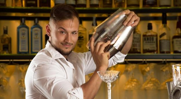 Очаровательный бармен готовит коктейли в двух шейкерах.