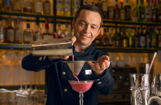 Charming bartender prepares a delicious cocktail. strain the drink through a strainer and pour into a cocktail glass
