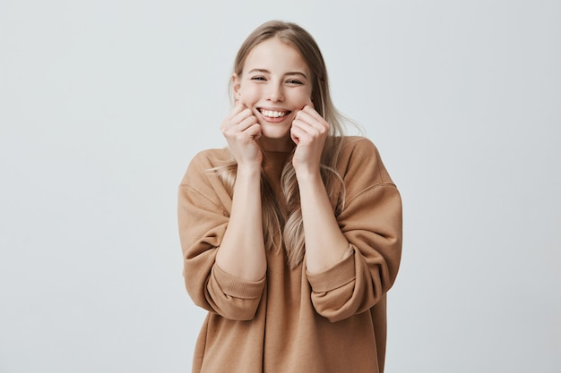Charming beautiful female model smiling broadly wearing brown sweater, pinching her cheeks, mocking, having good mood and fun. positive emotions and feelings