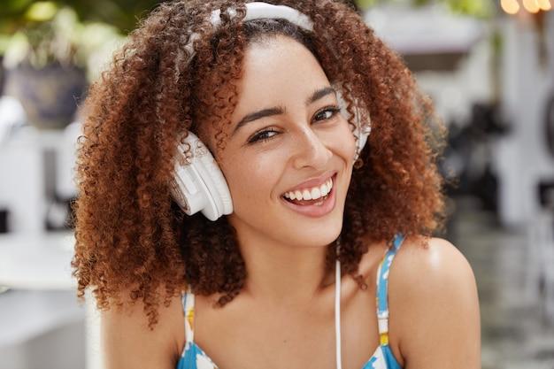 Affascinante bella studentessa ascolta lezioni audio in cuffie digitali, ha un'espressione felice.