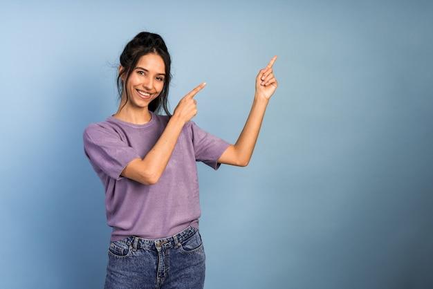 黒髪の魅力的で美しい女の子が指で指しています