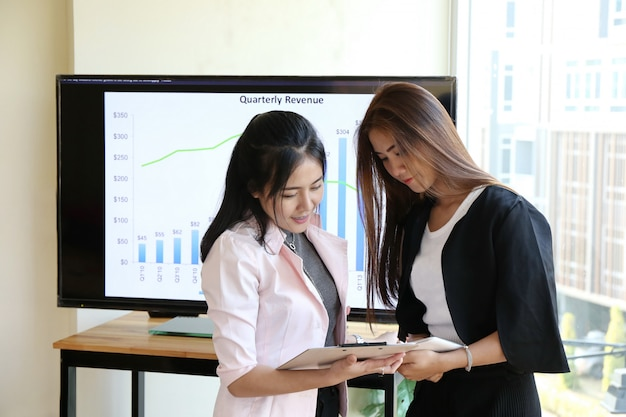 Charming beautiful tan skin asian chic smart woman hand work on laptop phone and write pen on notebook dairy on wooden table in office. presenting your product with woman good job performance.