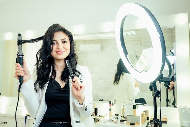 ヘアスタイルをやっていて、スタジオビューティーサロンの鏡の前でヘアアイロンを手に持っている魅力的な美しい女性の美容師スタイリスト。セルフケアと自己愛の概念