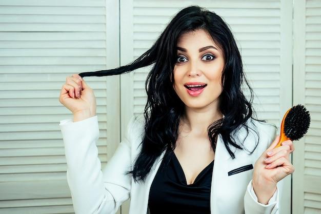 ヘアスタイルをやっていて、スタジオビューティーサロンでヘアブラシを手に持っている魅力的な美しい女性の美容師スタイリスト。セルフケアとヘアケアの概念