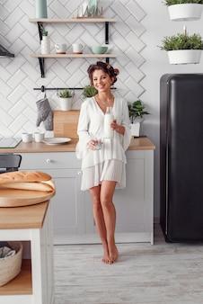 Очаровательная красивая женщина держит бутылку молока. красивая девушка готовит завтрак в современной уютной кухне.