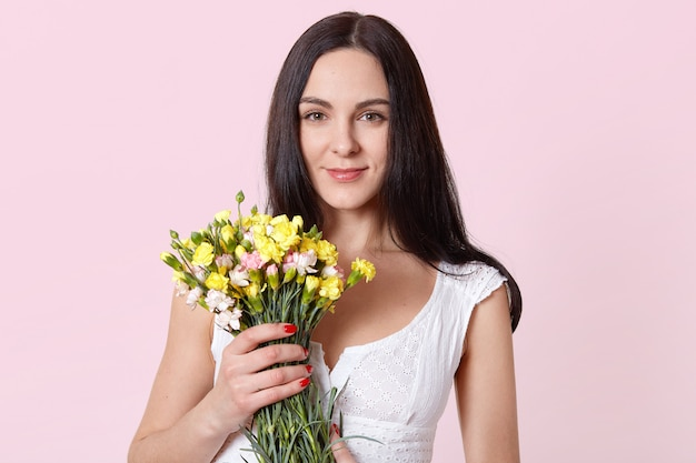 Charming beautiful woman holds yellow pink flowers with one hand, looking directly at camera, feels pleased.