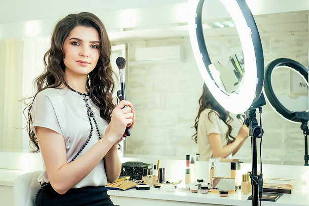 매력적인 미녀 메이크업 아티스트(visagiste)는 거울 앞에 앉아 스튜디오에서 화장용 브러쉬를 들고 있다