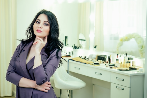 매력적인 아름다운 여성 전문 메이크업 아티스트(visagiste)는 스튜디오 미용실의 거울 앞에 서 있습니다.