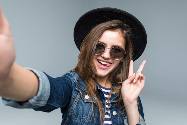La bella donna affascinante con il gesto di pace in cappello nero e gli occhiali da sole prendono il selfie dalle mani su fondo grigio
