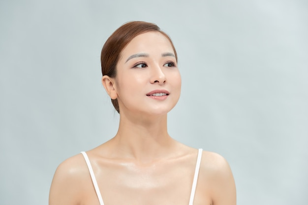 自宅で魅力的な美しい若いアジアの女性のスキンケア