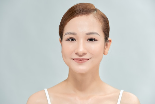顔に触れる魅力的な美しい若いアジアの女性