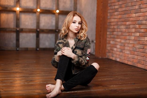 グレーのtシャツと黒のファッショナブルな破れたジーンズのスタイリッシュなミリタリーカモフラージュヴィンテージジャケットの魅力的な美しい若い女性は、レンガの壁とライトの近くのモダンなスタジオに座っています。かわいい女の子