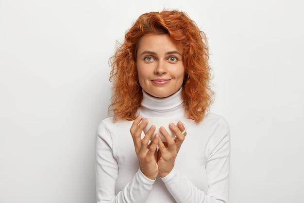 Affascinante e bella giovane donna sta con una tazza di tè, ha un piccolo sorriso sul viso, gode di bevande calde nel fine settimana, ha i capelli rossi, indossa un collo casual. tutto in colore bianco. monocromo