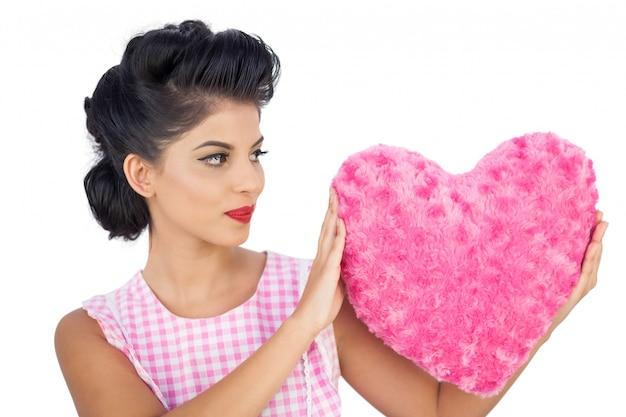 핑크 하트 모양의 베개를 들고 매력적인 검은 머리 모델