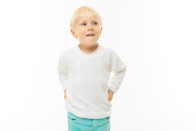 Charming blond boy in a white t-shirt thinking on a white wall