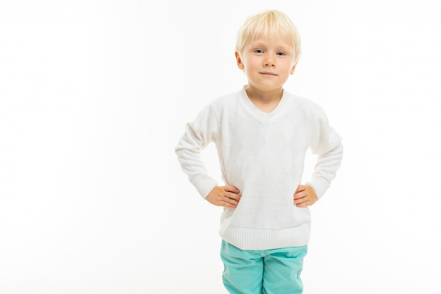 Charming blond boy in a white t-shirt on a white wall with blank space