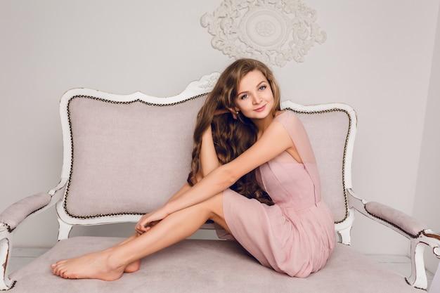 ソファーに座っている魅力的なブロンドの女の子。彼女は長い巻き毛を持ち、彼女の足に彼女の手を保持しています。