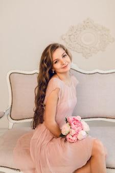 Affascinante ragazza bionda seduta su un divano. ha lunghi capelli ricci e tiene in mano un mazzo di peonie.