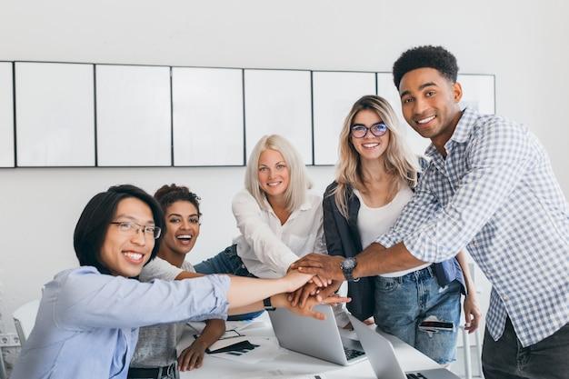 Очаровательная блондинка сотрудник веселится с коллегами и позирует для фото в светлой комнате. команда it-специалистов завершила тяжелый бизнес-проект рукопожатием.