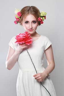 Charming blonde flowers hair and in her hands