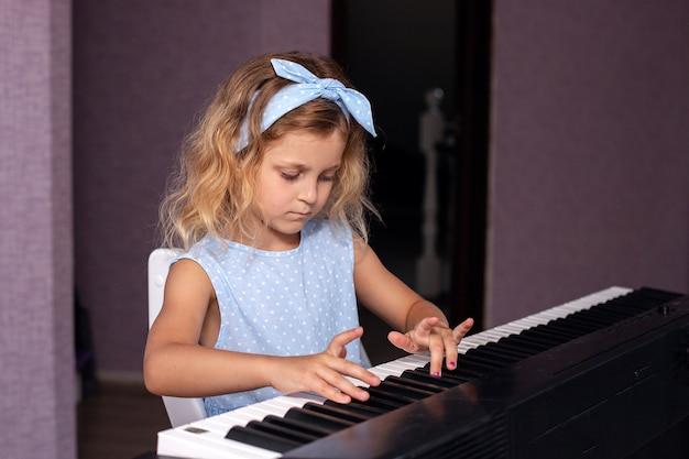 A charming blonde girl in a blue dress plays the piano in her bedroom
