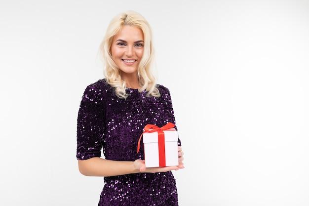 보라색 빛나는 드레스에 매력적인 금발 소녀는 신중하게 복사 공간 흰색 배경에 선물 상자를 보유하고