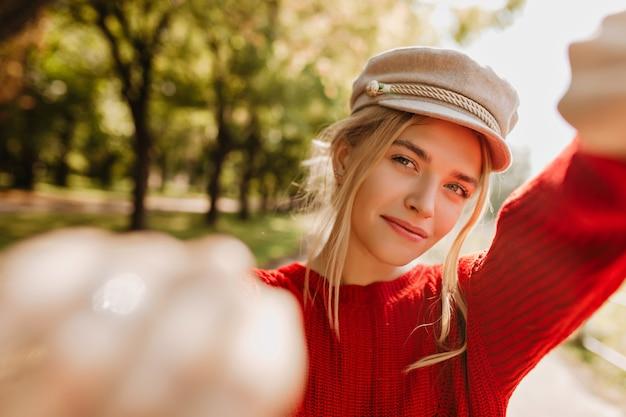 秋の公園で自分撮りを作る明るい流行の帽子と赤いセーターの魅力的なブロンドの女の子。