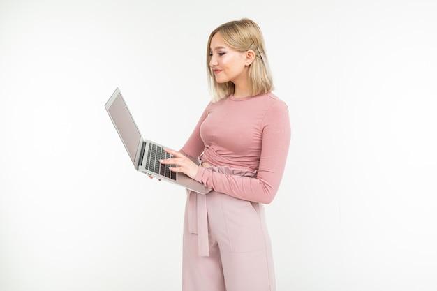 매력적인 금발 소녀 흰색 스튜디오 배경에 그녀의 손에 잡고 노트북 컴퓨터 키보드에 입력합니다.