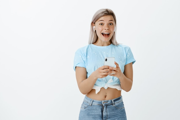 Affascinante ragazza bionda in posa in studio con il suo telefono e auricolari