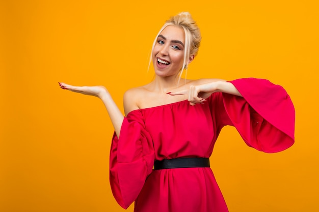 Charming blonde girl in a red dress with holding hand on a yellow studio surface