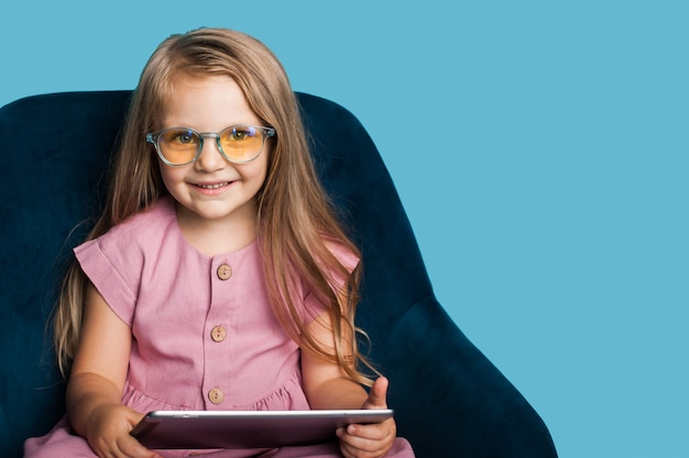 안경 매력적인 금발 소녀는 의자에 태블릿을 들고 여유 공간이있는 파란색 스튜디오 벽에 포즈 미소