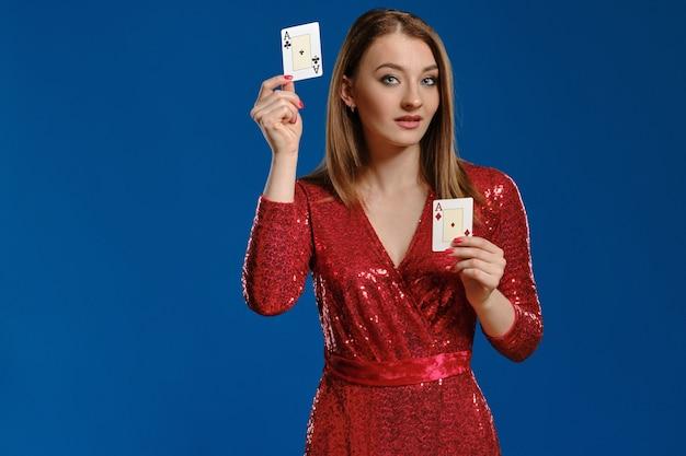 Очаровательная блондинка с макияжем, в красном платье с пайетками показывает две игральные карты, позирует на синем фоне. азартные развлечения, покер, казино. крупный план.
