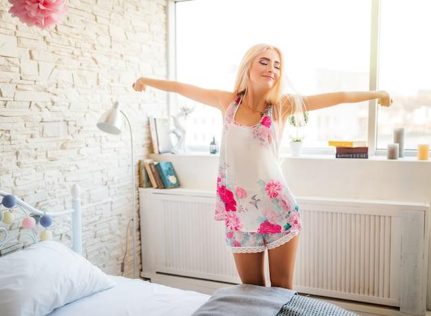 섬세한 수면 복을 입은 매력적인 금발은 새로운 하루를 즐기고 아침에는 창문에 뻗어 있습니다.