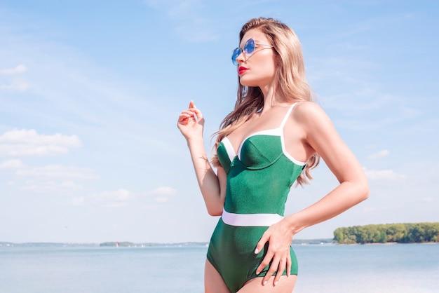 녹색 수영복을 입은 매력적인 금발이 고급 호텔 해변에서 포즈를 취하고 있습니다. 여행, 관광, 레크리에이션의 개념입니다. 혼합 매체