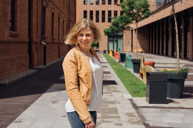 魅力的な金髪は街の通りで春の日を楽しんでいて、カメラライフを見ながら笑顔は...