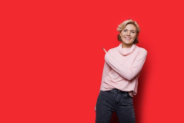 Очаровательная блондинка, указывая на красное свободное пространство рядом с ней, улыбаясь в камеру