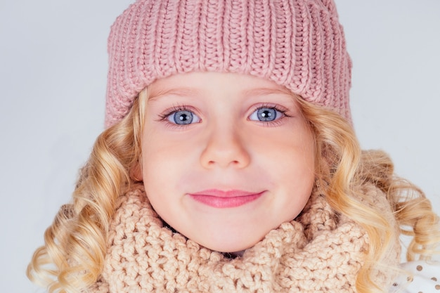 スタジオで白い背景にニットピンクの帽子とかわいいスカーフを身に着けている魅力的な金髪の少女の大きな青い目。ファッション秋冬シーズンセールコンセプト。願い事クリスマスの夜と誕生日を作る