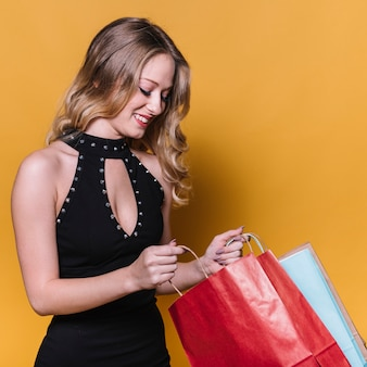 Charming blonde looking inside of shopping bags