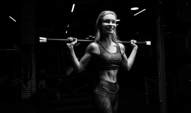 Очаровательная блондинка позирует в тренажерном зале с боди-баром. передний план. понятие о спорте, бодибилдинге, фитнесе. смешанная техника