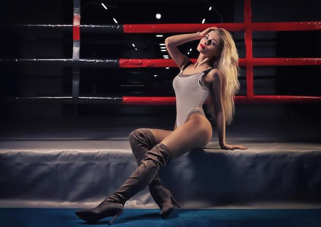 링 근처에서 포즈를 취하는 매력적인 금발. 권투, 이종격투기, 패션, 뷰티의 개념. 혼합 매체