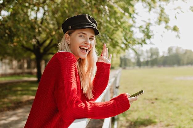 彼女の携帯電話を持って幸せそうに笑っている魅力的なブロンド。日当たりの良い公園で良い一日を過ごしている輝く少女。