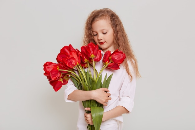 Charming blonde wavy haired girl wearing white blouse holding big bouquet of red tulips, looking at flowers with dreamy expression